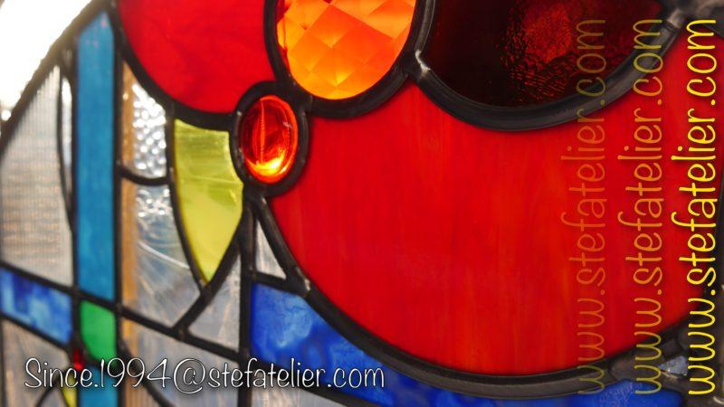 gros plan vitrail moderne verres à reliefs et cabochons rouges